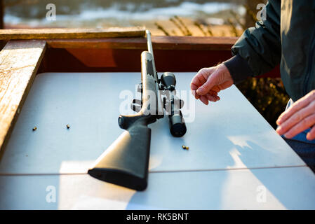 A man holds a 22 caliber rifle with a scope as a hunting gun in the United States. - Stock Image