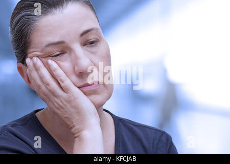 Middle aged woman nearly falling asleep in the office. Tiredness because of sleep apnea syndrome, insomnia or fibromyalgia, - Stock Image