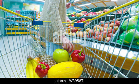 Woman with cart or trolley buying fresh vegetables and fruits at supermarket - Stock Image