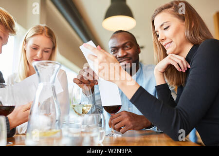 Group of guests in the bistro or restaurant read the menu and think twice - Stock Image