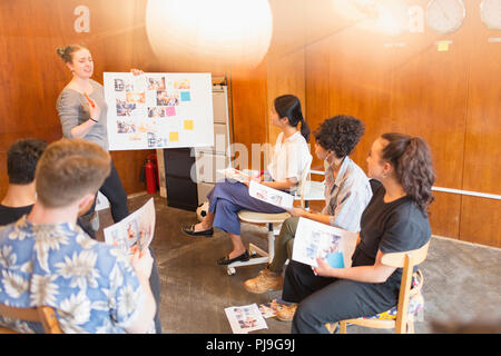 Creative designers brainstorming, reviewing photograph proofs in office meeting - Stock Image