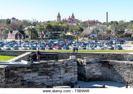 Flagler College is visible over the ravelin and parking lot of the Castillo de San Marcos, a Spanish fortification at St. Augustine, Florida USA - Stock Image