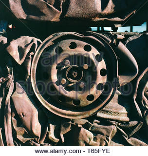 A crushed motor vehicle, showing the remains of a wheel. Birmingham, UK. - Stock Image