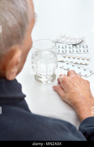 Old woman sitting at a table in her kitchen or living room with a glass of water and different tablets in blister packs - Stock Image