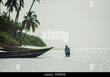 A man wades in the sea in the Turtle Islands, Sierra Leone. - Stock Image