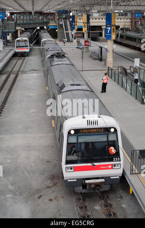 An electric train prepares to leave the Perth central railway station on the Fremantle line. - Stock Image