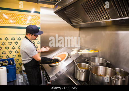 Man cooking in commercial kitchen of food truck - Stock Image