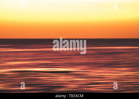 Artistic view of ocean sea water in long exposure in motion - background and coulours for nature concept - outdoors holiday vacation - Stock Image