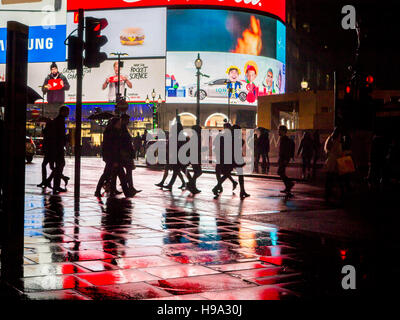 Rain reflects Piccadilly Circus lights in Central London - Stock Image