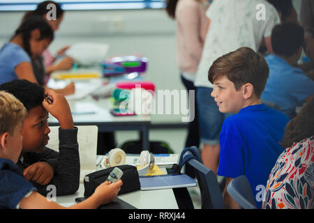 Junior high school boy students talking in classroom - Stock Image