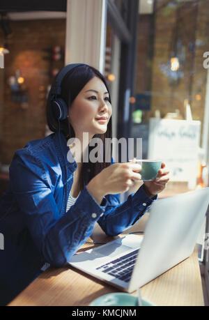Pensive young woman listening to music with headphones and drinking coffee at laptop in cafe window - Stock Image