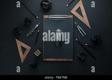 Building and construction concept, the light bulb of an idea on a dark background with compasses, pencils, and rulers. - Stock Image
