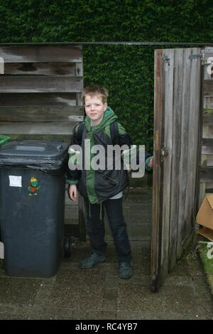 Young boy age 8 arrives from school , at the garden gate. - Stock Image