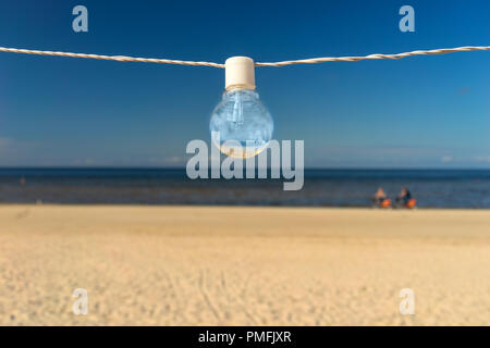 Light bulb on the wire on the beach - Stock Image