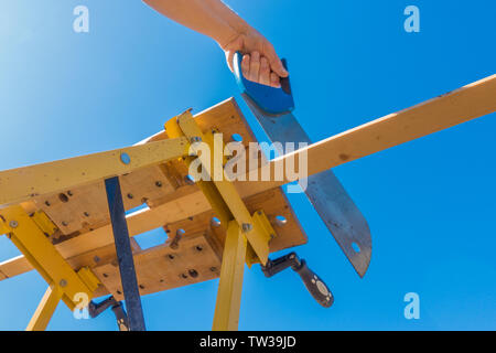 Close POV shot from below of a man's hands sawing the end off a piece of wood, which is clamped in a portable workbench, outside against a blue sky. - Stock Image