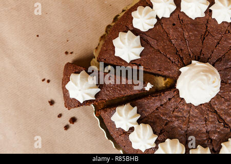 Ordinary brownie cake cut with one piece extended and copy space on the left on brown eco paper - Stock Image