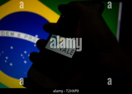 Vale SA, Brazilian metals and mining multinational corporation and logistics operator, logo is shown on smartphone display, Brazil flag on background - Stock Image