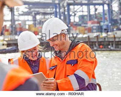 Dock workers communicating with supervisor at docks infront of huge cargo ship leaving docks - Stock Image