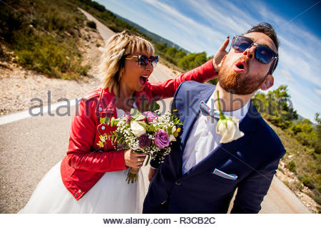 Bride slaps her boyfriend in the back of the head and he spits out a flower he was carrying in his mouth. - Stock Image