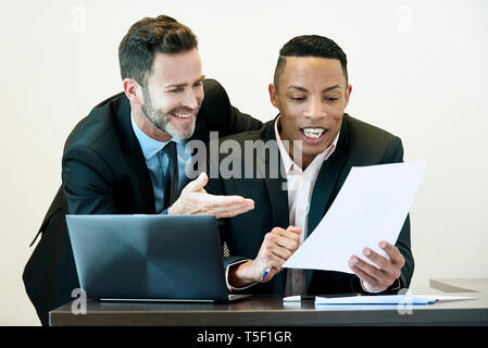 Businessmen discussing document at desk in office - Stock Image