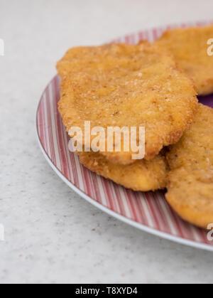 Golden Wiener schnitzel on plate - Stock Image