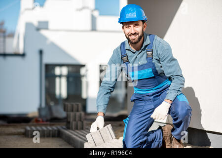 Portrait of a builder in uniform laying paving tiles on the construction site with white houses on the background - Stock Image