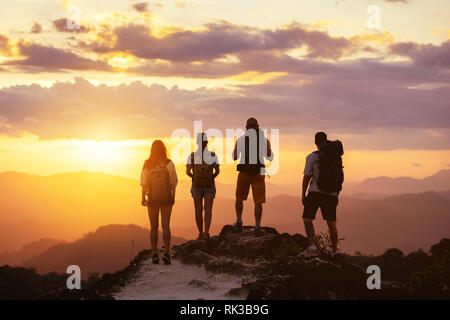 Group of four peope's silhouettes stands on mountain top and looks at sunset - Stock Image