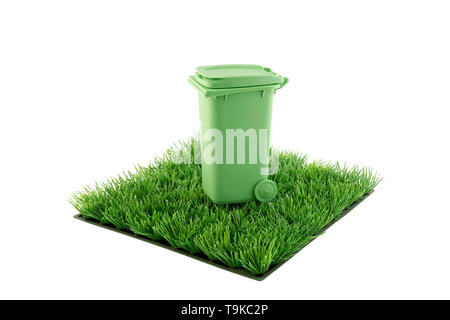 Green recycle bin on square of green grass field isolated on white background - Stock Image