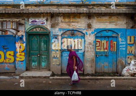 Poverty in Chennai, India, where a shopper carries her bag of shopping - Stock Image