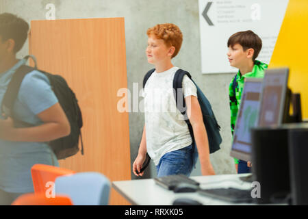 Junior high boy students walking in library - Stock Image