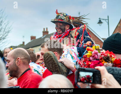 Haxey, Lincolnshire, England, UK – The Fool, with black face, carried ny The Boggins singing traditional folksongs in the ancient custom of The Haxey Hood since the 14th Century - Stock Image
