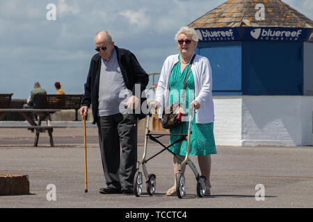 An elderly couple taking a walk together, one using a walking stick and one using a mobility aid or zimmer frame - Stock Image