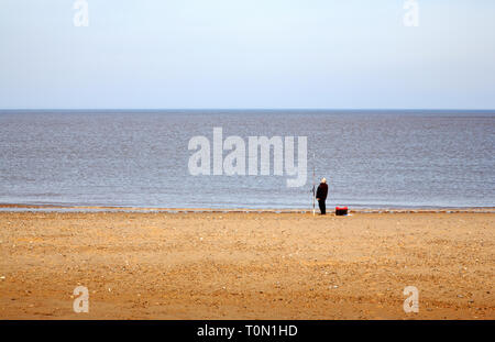 A lone sea angler on a North Norfolk beach at Bacton-on-Sea, Norfolk, England, United Kingdom, Europe. - Stock Image
