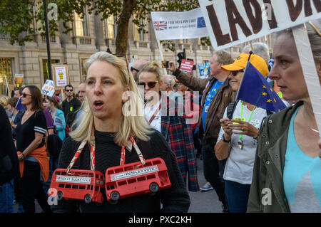 London, UK. 20th October 2018. A woman with two model red buses around her neck carrying the message 'Brexit Sucks - lets have a People's Vote' at the end of the People's Vote March calling for a vote to give the final say on the Brexit deal or failure to get a deal. They say the new evidence which has come out since the referendum makes it essential to get a new mandate from the people to leave the EU. With so many on the march the crowding meant many failed to reach Parliament Square and came to a halt in Whitehall. Peter Marshall/Alamy Live News - Stock Image