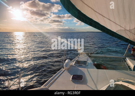 sailing with a catamaran on the ocean , end of day lightning. - Stock Image