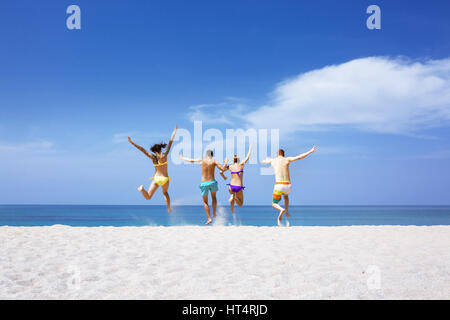 Happy friends on lonely beach - Stock Image