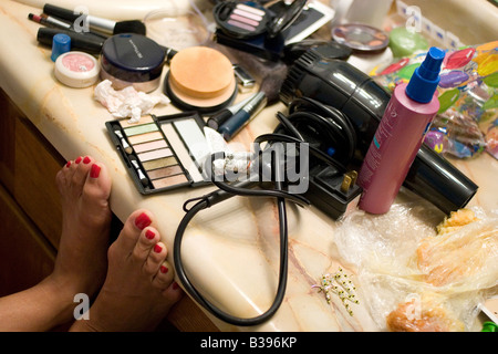 A woman rests her feet on a vanity while getting her makeup done on her wedding day in Bentonville, Arkansas, U.S.A. - Stock Image