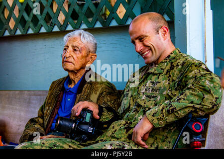 "(l) Retired U.S. Army Special Operations Command Master Sgt. Polito ""Paul"" Olivas talks with U.S. Navy Chief Mass Communications Specialist William Tonaccho before going Airborne to celebrate his 100th birthday at Skydive Hawaii at Dillingham Airfield, Hawaii, Aug. 29, 2018. Olivas joined the U.S. Army prior to World War II where he earned his mustard stained jump winds. (U.S. Army Photo by Sgt. 1st Class Timothy D. Hughes/28th PAD) - Stock Image"