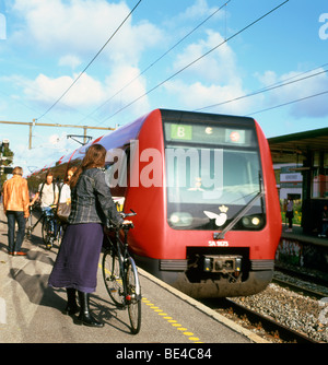 A woman waiting on the station platform to put her bicycle on a train Gentofte Copenhagen Denmark - Stock Image