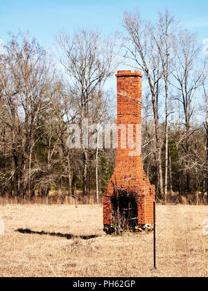 Old rustic brick solitary house chimney left standing in a field in Alabama, USA. - Stock Image