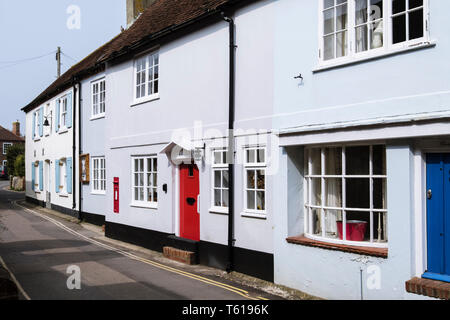 Old houses with flood defenses at front door on narrow street close to seafront. Bosham, Chichester, West Sussex, England, UK, Britain - Stock Image