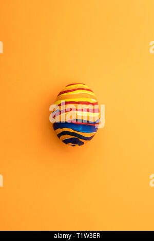 Detail of painted yellow Easter egg with red and blue stripes in orange background. - Stock Image