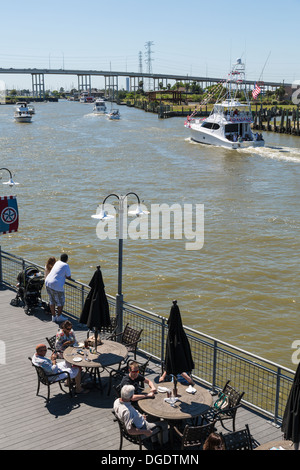 Tourists eating outside at Kemah boardwalk amusement park as boats sail past - Stock Image