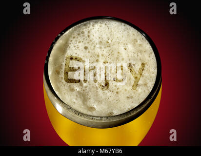 A glass of lager with the word 'Enjoy' written in the foam, shown against a red and black graduated background - Stock Image
