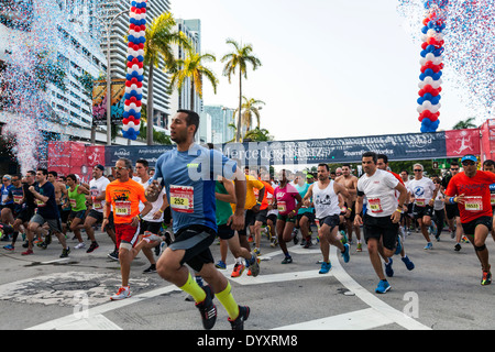 Male runners sprinting away from crowded starting line of 2014 Mercedes-Benz Corporate Run in Miami, Florida, USA. - Stock Image
