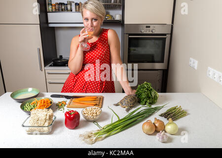 Woman drinks from wine glass in kitchen while tortoise eats salad - Stock Image