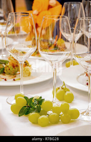 wedding festive table champagne glasses and bunches of grapes - Stock Image
