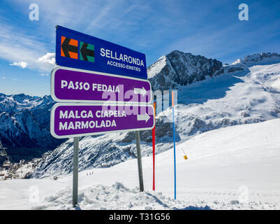 Picture of a sign indicating slopes and towns (Passo Fedaia, Malga Ciapela, Marmolada) and the access to the Sellaronda circuit, Dolomites, Italy - Stock Image