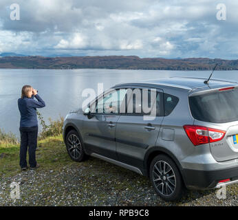 Tourist admires far reaching views over Loch Slapin and Eishort from high on a coastal road at Drinan near Elgol on the isle of Skye, Scotland, UK - Stock Image