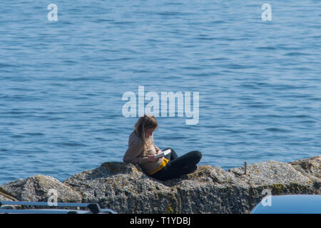 Mousehole, Cornwall, UK. 29th Mar, 2019. UK Weather. A woman making the most of the lovely weather, reading a book on harbour wall overlooking the sea at Mousehole Credit: Simon Maycock/Alamy Live News - Stock Image
